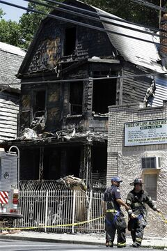 Firefighters and police work near the rubble of a burned out home as they look for clues to a fire that authorities say killed six people in Newark, N.J., Sunday, June 16, 2014. The Essex County prosecutor's office says the fast-moving fire that roared through a single-family home in New Jersey's largest city, broke out at around 4 a.m. Sunday. (AP Photo/Mel Evans)