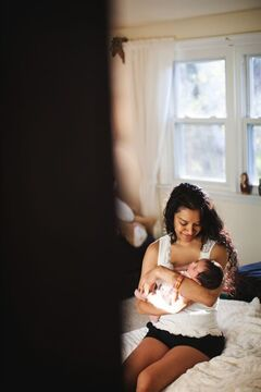 This 2013 photo provided by I Heart New York shows Anzalee Rhodes holding her 10-day-old daughter Arabelle in her Long Island home. Rhodes and her husband Kristain Rhodes are hiring photographers from I Heart New York to document their experiences watching their daughter grow. Hiring professional photographers to capture everyday life and not just important events like weddings has become a lifestyles trend. (AP Photo/I Heart New York)