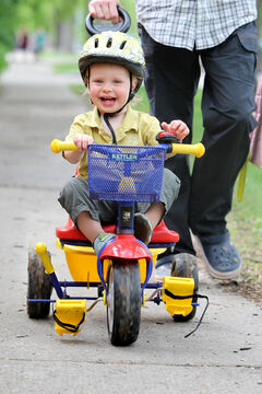 18-month-old Jamie Main Prize laughs while going for a ride on his trike with dad.