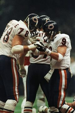 FILE - This Jan. 26, 1986 file photo shows Chicago Bears quarterback, Jim McMahon (9) bumping helmets with Keith Van Horne during Super Bowl XX in New Orleans. A group of retired NFL players says in a lawsuit filed Tuesday that the league, thirsty for profits, illegally supplied them with risky narcotics and other painkillers that numbed their injuries for games and led to medical complications down the road. The complaint names eight players, including three members of the Super Bowl champion 1985 Chicago Bears: defensive lineman Richard Dent, offensive lineman Keith Van Horne, and quarterback Jim McMahon. Lawyers seek class-action status, and they say in the filing that more than 400 other former players have signed on to the lawsuit. (AP Photo/Eric Risberg, File)