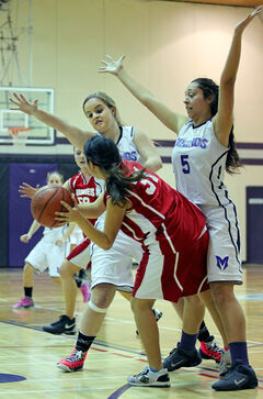 Jessi Coulter and Zaina Bird (right) of the Vincent Massey Vikings defend against a Hamiota Huskies player during varsity girls' action in the Neelin Invitational Tournament Friday.
