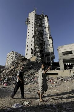 Palestinians walk in front of the damage of the Italian Complex following several late night Israeli airstrikes in Gaza City, in the northern Gaza Strip, Tuesday, Aug. 26, 2014. Israel bombed two Gaza City high-rises with dozens of homes and shops Tuesday, collapsing the 15-storey Basha Tower and severely damaging the Italian Complex in a further escalation in seven weeks of cross-border fighting with Hamas. (AP Photo/Adel Hana)