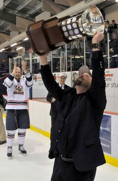 Kings head coach Marlin Murray -- with assistant David Anning in the background -- hoists the Anavet Cup trophy in 2010.