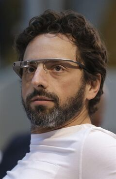 Google co-rounder Sergey Brin, left, wears Google Glass glasses at an announcement for the Breakthrough Prize in Life Sciences at Genentech Hall on UCSF's Mission Bay campus in San Francisco, Wednesday, Feb. 20, 2013. Google is giving more people a chance to pay $1,500 for a pair of the Internet-connected glasses that the company is touting as the next breakthrough in mobile computing. The product, dubbed