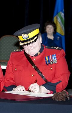 RCMP Assistant Commissioner Marianne Ryan signs the Change of Command parchments as Her Honour Mrs. Linda Ethell looks on during a ceremony in Edmonton on Wednesday, January 29, 2014. THE CANADIAN PRESS/HO - RCMP