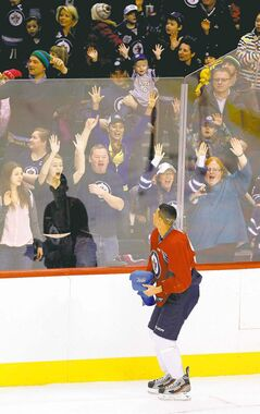 Winnipeg Jets forward Evander Kane throws hats to fans on opening day of training camp at the MTS Centre on Sunday.
