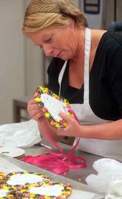"Volunteer Brenda Appelt strings a ribbon through a gingerbread cookie, called a Lebkuchen Herzen or ""love cake,"" for the German pavilion during food preparations at Crocus Plains high school on Friday afternoon."