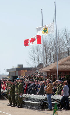 Flags are lowered to half-mast during a minute of silence held during the National Day of Honour ceremony at CFB Shilo on Friday.