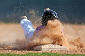 Dylan Borskiewich of the Vincent Massey Vikings dives back to first base kicking up a cloud of dust during Prairie West High School Baseball action against the Dauphin Clippers at Andrews Field on Wednesday.