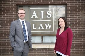 Lawyer Andrew Synyshyn and office administrator Danielle Guenther  stand outside Synyshyn's new law firm, AJS Law, on 10th Street on Thursday.