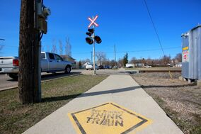 A sidewalk stencil warns sidewalk users of the train crossing on 6th Street just south of McTavish Avenue on Tuesday afternoon.