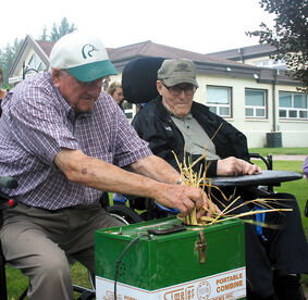 Lifelong farmers Red McConnell (left) and Harry Gardham use the portable combine on the mini crops planted at Birch Lodge Personal Care Home in Hamiota on Thursday.