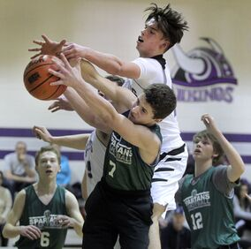 Jayden Engel of the Vincent Massey Vikings goes over top of Neelin Spartan Cauy Farthing in a battle for a rebound during Game 1 of the Brandon High School Basketball League junior varsity boys' final at Massey on Wednesday evening.