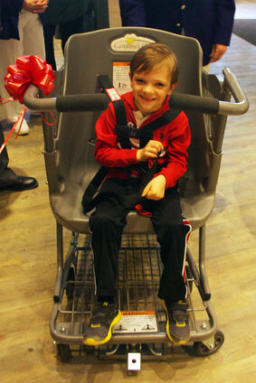 Zander Wallin, 6 — who suffers from cerebral palsy — straps in to Caroline's Cart, a special shopping cart designed for older children with disabilities, during an event at Safeway in the Corral Centre on Monday. The Elks of Canada in partnership with Safeway presented the first Caroline's Cart in Brandon. There are 50 such carts in grocery stores in Western Canada.