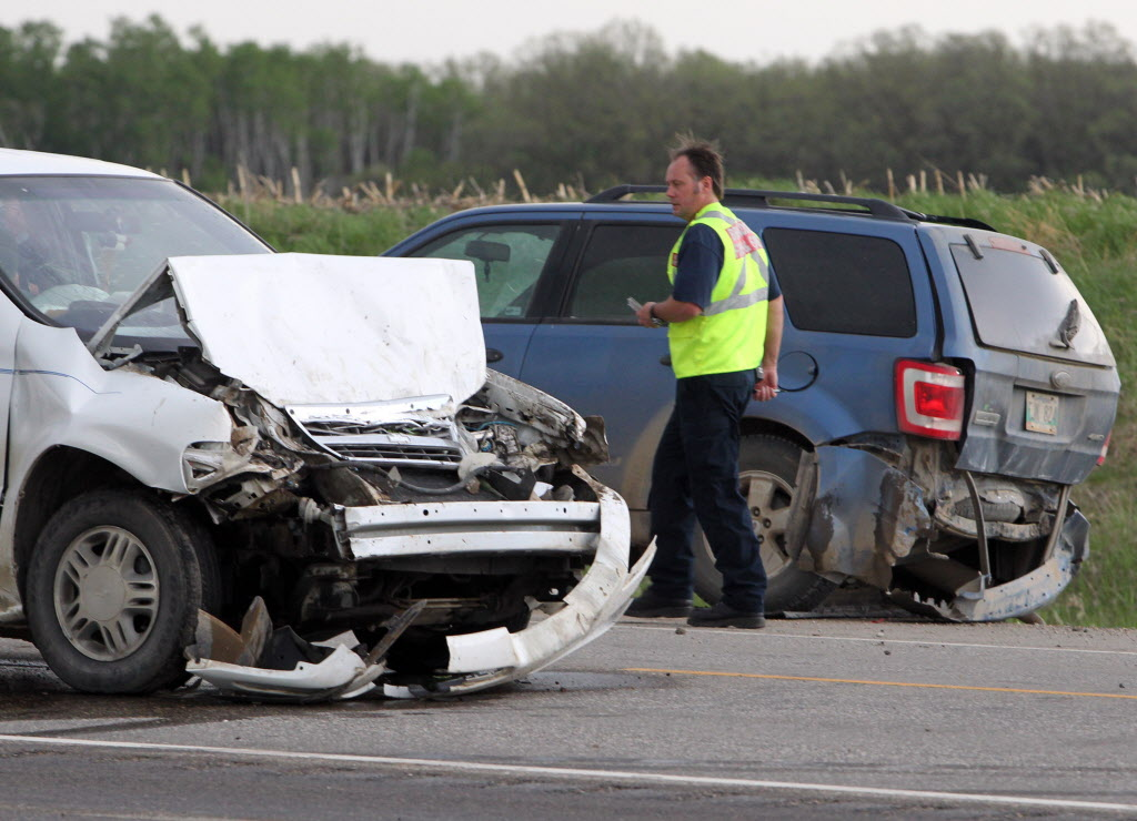 Emergency crews walk amid the wreckage after a two-vehicle crash on Highway 10 near Tower Road this spring.