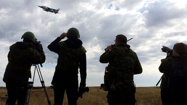 Soldiers and media members look up to an Alpha jet fighter on a low flyby during field exercises with the 1st Regiment, Royal Canadian Horse Artillery at CFB Shilo on Tuesday morning. The exercises involved artillery gunners working with forward observers and aircraft to hit precise targets.
