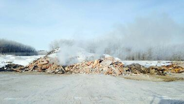 Workers set fire to building debris from the former ski chalet at a nearby landfill site.