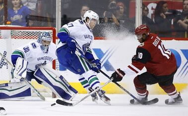 Arizona Coyotes' Anthony Duclair (10) tries to get off a shot past Vancouver Canucks' Ben Hutton (27) as Canucks' goalie Ryan Miller (30) gets in position for the save during the first period of an NHL hockey game Wednesday, Feb. 10, 2016, in Glendale, Ariz. (AP Photo/Ross D. Franklin)