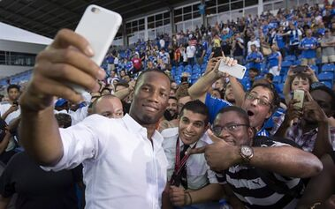 Montreal Impact's newest player Didier Drogba takes a selfie with fans following a news conference Thursday, July 30, 2015 in Montreal. THE CANADIAN PRESS/Paul Chiasson