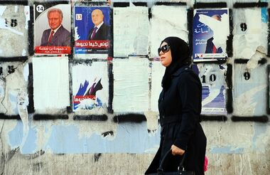 A woman walks past a wall plastered with electoral campaign posters two days before the first round of the presidential elections in Tunis, Tunisia, Friday, Nov. 21, 2014. Tunisia's presidential election represents the final phase in a torturous and difficult transition to democracy since Tunisians overthrew Ben Ali in January 2011 — sparking the Arab Spring protests that ousted autocrats across the Middle East. (AP Photo/Hassene Dridi)