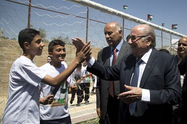FIFA President Sepp Blatter meets Palestinian kids during the inauguration of a football stadium in the village Dura Al-Qari' near the West Bank city of Ramallah, Wednesday, May 20, 2015. FIFA President Sepp Blatter said Tuesday he is on a