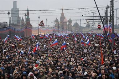 "People carry Russian national flags during a march in memory of opposition leader Boris Nemtsov who was gunned down on Friday, Feb. 27, 2015 near the Kremlin, with The Kremlin Wall and St. Basil Cathedral in the background in Moscow, Russia, Sunday, March 1, 2015. Thousands converged Sunday in central Moscow to mourn veteran liberal politician Boris Nemtsov, whose killing on the streets of the capital has shaken Russia's beleaguered opposition. They carried flowers, portraits and white signs that said ""I am not afraid."" (AP Photo/Dmitry Lovetsky)"