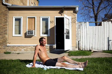 Will Boon takes advantage of the record hot temperatures and sunbathes in front of his residence on Third Street on Thursday.