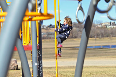 Hayley Perras climbs a play structure at the Riverbank Discovery Centre while playing with her sister Avery on Monday afternoon.