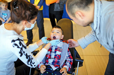 Yi Fan Dong, 3, has his teeth checked by dentist Dr. Elham Elahiyoun, left, during the Preschool Wellness Fair at the Keystone Centre on Tuesday.