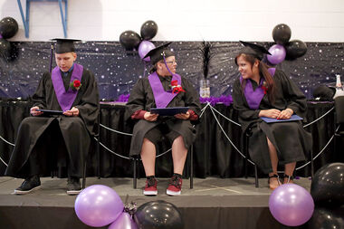 Graduates Shayla Pratt, centre, and Kendra Ironman, right, chat alongside fellow graduate Brent Mentuck during the Sioux Valley High School graduation ceremony on Thursday.
