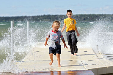 Three-year-old Nolan Edwards and his six-year-old brother Jordon of Onanole run through the spray caused by large waves hitting the dock while enjoying the waves caused by high winds at Clear Lake in Riding Mountain National Park on Wednesday.
