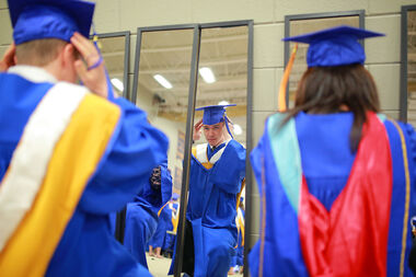 David Smith, a physical education graduate, adjusts his mortar board in the mirror prior to the afternoon convocation at the Brandon University Healthy Living Centre on Friday.