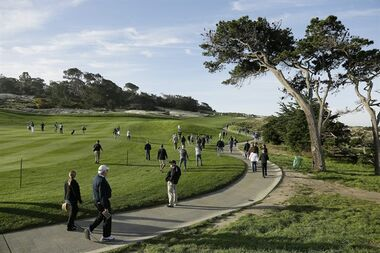 Spectators make their way along the second hole of the Spyglass Hill Golf Course while following a group that included Mark Wahlberg and Bubba Watson during the first round of the AT&T Pebble Beach National Pro-Am golf tournament Thursday, Feb. 11, 2016, in Pebble Beach, Calif. (AP Photo/Eric Risberg)