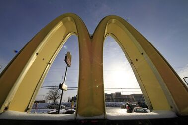 Cars drive past the McDonald's Golden Arches logo at a McDonald's restaurant in Robinson Township, Pa., Jan.21, 2014. McDonald's has launched the latest salvo in a battle for the stomachs of food-conscious Canadians with new ads that picture hamburger buns floating over an empty space where the patty should be.