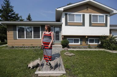 Sarah Fehr is photographed with her dogs Werner and Bowser at her home which previously contained a drug grow-op in Winnipeg, Sunday, June 28, 2015. Fehr and her husband bought the home knowing of it's history. Some face financial difficulties when they buy or win a house that was formerly a grow-op. Seems once the house it denoted as that by the police, it forever more bears the black mark. THE CANADIAN PRESS/John Woods