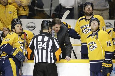 Referee Graham Skiliter (24) explains to Nashville Predators head coach Peter Laviolette why a goal by defenseman Seth Jones, not shown, was waved off in the second period of an NHL hockey game against the Edmonton Oilers Thursday, Nov. 27, 2014, in Nashville, Tenn. (AP Photo/Mark Humphrey)