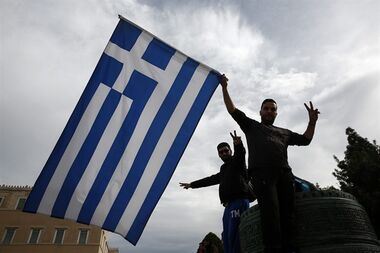 Farmers wave a Greek flag during an anti-government rally in front of the parliament in Athens, on Saturday, Feb. 13, 2016. Farmers from across Greece gather in Athens for a two-day protest against the government and its plans to impose new tax hikes and pension charges. Bailout lenders are demanding that Greece scrap tax breaks for farmers and impose pension reforms that will lead to higher monthly contributions from the self employed and salaried employees. (AP Photo/Yorgos Karahalis)