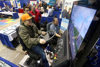 McCreary School Grade 12 student Tyson Mallett tries his hand behind the wheel of a semi-truck at the driving simulator used by First Class Training Centre at the 30th annual Brandon Career Symposium on Tuesday morning.