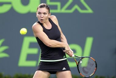 Simona Halep, of Romania, returns a shot from Sloane Stephens at the Miami Open tennis tournament, Wednesday, April 1, 2015 in Key Biscayne, Fla. (AP Photo/Wilfredo Lee)
