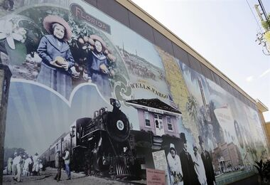In this Wednesday, July 30, 2014 photo, a mural shows Marie and Hazel Kirch holding oranges in 1914, and the Orange Blossom Special train which brought passengers to Lake Wales in the 1920's, in downtown Lake Wales, Fla. Oranges and grapefruits have been farmed commercially in Florida since the 1800's. Florida's $9 billion citrus industry is facing its biggest threat yet by a tiny invasive bug called the Asian Citrus Psyllid, which carries bacteria that are left behind when the psyllid feeds on a citrus tree's leaves. (AP Photo/Lynne Sladky)