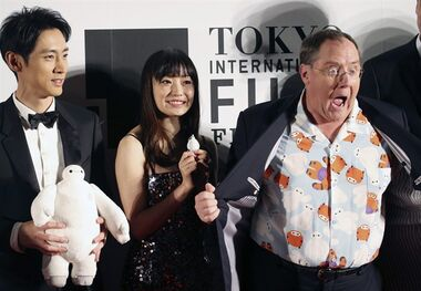 FILE - In this Thursday, Oct. 23, 2014 file photo, John Lasetter, right, chief creative officer at Pixar, Walt Disney Aniamation Studios and Disney Toon Studios, poses for a photo with Japanese actors, Miho Kanno, center, and Kotaro Koizumi, both holding a character of