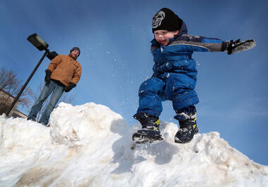 Mikhail Oleson leaps off a snowbank while playing with his father Elliot and brother Kier (not seen) near Princess Avenue on Monday.