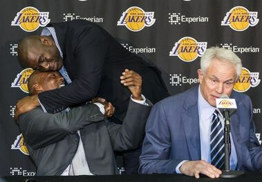 Byron Scott, bottom left, is hugged by former teammate Magic Johnson, left, as Scott is introduced by Los Angeles Lakers General Manager Mitch Kupchak, right, as the successor to Mike D'Antoni as the Lakers' head coach during a news conference in Los Angeles Tuesday, July 29, 2014. Scott is coming home for his fourth NBA coaching job. He inherits a team that missed the playoffs for just the third time in 38 years. (AP Photo/Damian Dovarganes)