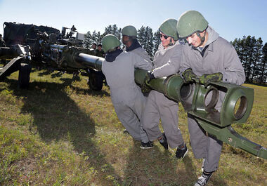 Brandon Wheat Kings players, including Garrett Armour (left) and Rylan Bettens (right), struggle to move an M777 artillery gun during the team's annual Soldier For A Day event at CFB Shilo on Tuesday. The day saw the Wheaties learn to rappel down a tower, work with an artillery gun and ride in a light armoured vehicle with members of the military.