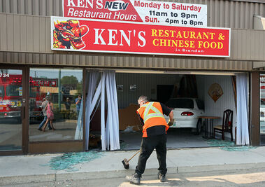 A tow truck driver sweeps up glass as a car rests inside the dining room of Ken's Restaurant & Chinese Food on the 700 block of 18th Street after the driver lost control and drove through the front window of the restaurant and into the side wall on Wednesday. No one was injured in the collision, but the restaurant was heavily damaged.