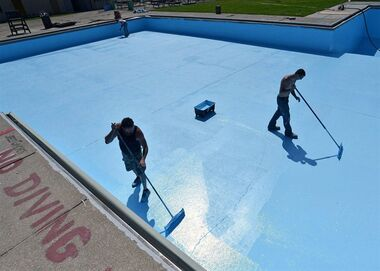 In this June 26, 2015 photo, Eric Peterson, 47, at left, and Joe Millspaw, 19, of Advanced Concrete Floor Finishes of Findley Lake, N.Y., paint the surface of the swimming pool at Rodger Young Park in Erie, Pa. U.S. service firms grew at a slightly faster pace in June, as business activity and new orders increased. (Christopher Millette/Erie Times-News via AP)