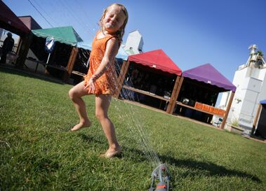 Elise Pohjolainen dashes through a cool blast of water from a sprinkler set up at the weekly Global Marketplace area at 12th Street and Rosser Avenue, Thursday afternoon. The market rents stalls to local artisans, craftspeople and gardeners to sell wares to locals through the season.
