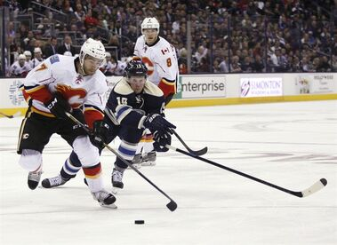 Columbus Blue Jackets' Ryan Johansen, right front,chases Calgary Flames' T J Brodie (7) during the second period of an NHL hockey game, Friday, Oct. 17, 2014 in Columbus, Ohio. (AP Photo/ Mike Munden)