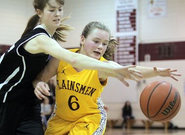 Alyssa Norman of the Crocus Plainsmen and Josie Grift of the Vincent Massey Vikings lunge for the ball during the first game of the best-of-three Brandon High School Basketball League varsity girls' final on Thursday evening at Crocus Plains.
