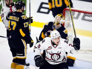Brandon Wheat King John Quenneville, left, and goalie Jordan Papirny look on as Red Deer Rebel Adam Musil celebrates his tying goal during Wednesday's Memorial Cup hockey game in Red Deer, Alta., on Wednesday.